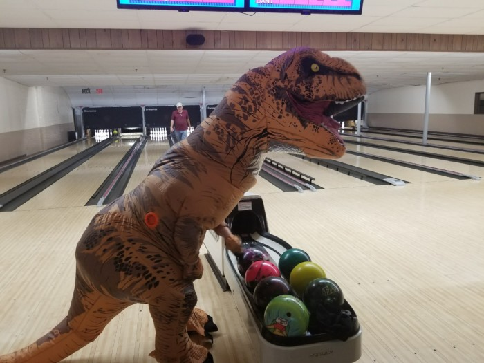 T-rex costume reaches for a ball at the bowling alley