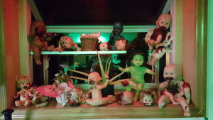 The green glow from the house and the red illumination from the light over the sink made these creepy baby dolls in kitchen window even worse