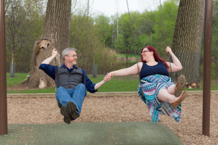 engagement photo session at a playground on the swings
