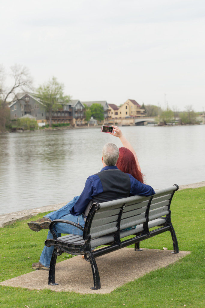 engagement photo session on a park bench taking a selfie