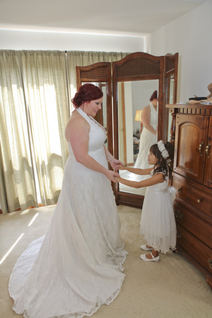 bride and flower gir bridal photo in front of a tri-fold mirror in bride's bedroom