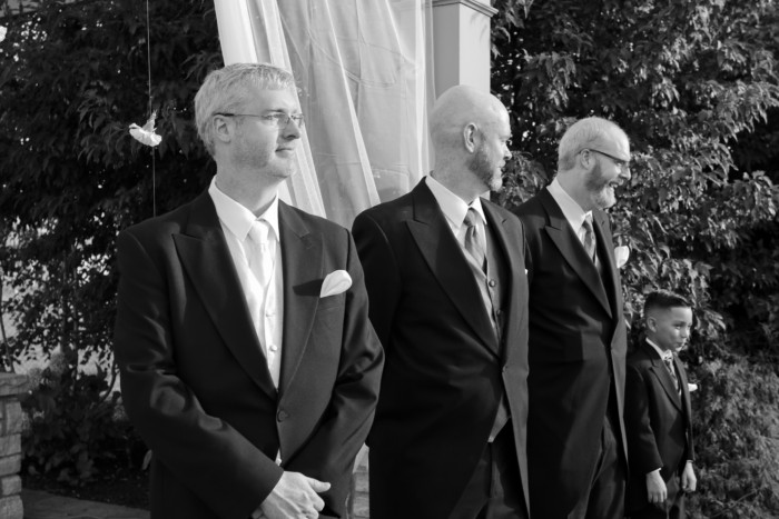 the groom, groomsmen, and junior groomsman at the alter