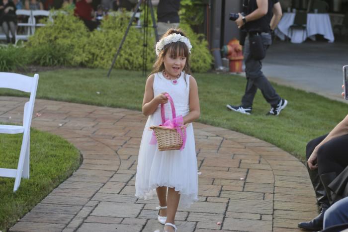 The flower girl threw pink rose petals