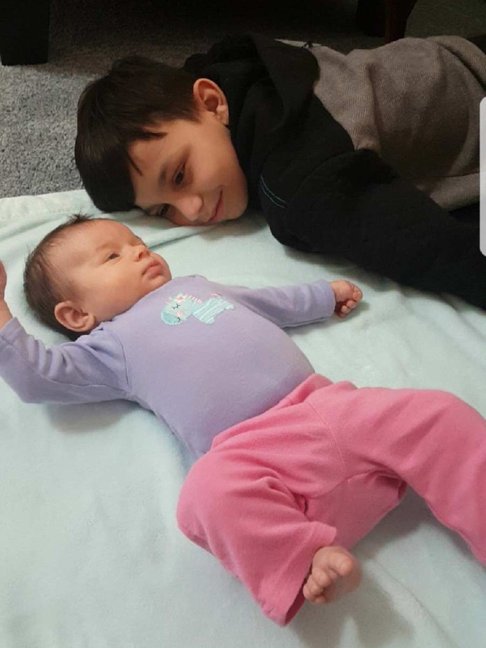 Preteen staring adoringly at his infant cousin