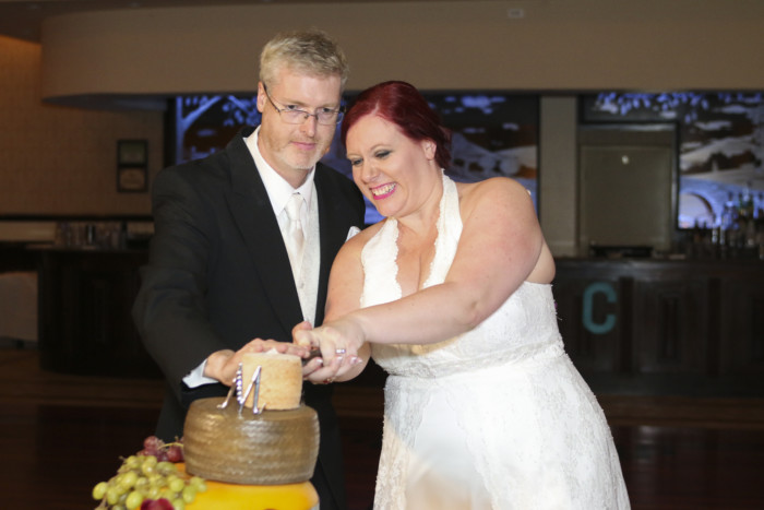 bride and groom cutting the top of the cheese wheel wedding cake