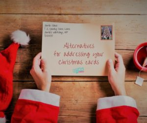 Santa holding an envelope that says alternatives for addressing your Christmas cards