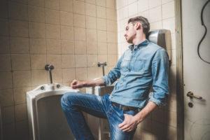 man falling asleep next to urinals