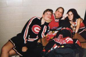Three girls blowing kisses in 90s high school cheerleading uniforms