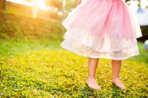 Unrecognizable little girl in pink princess skirt running barefoot in green sunny summer garden
