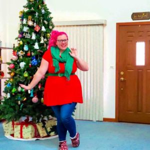 Chrissy in front of a Christmas tree