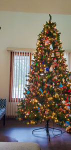 9-foot Christmas tree decorated with white and colored lights and ornaments