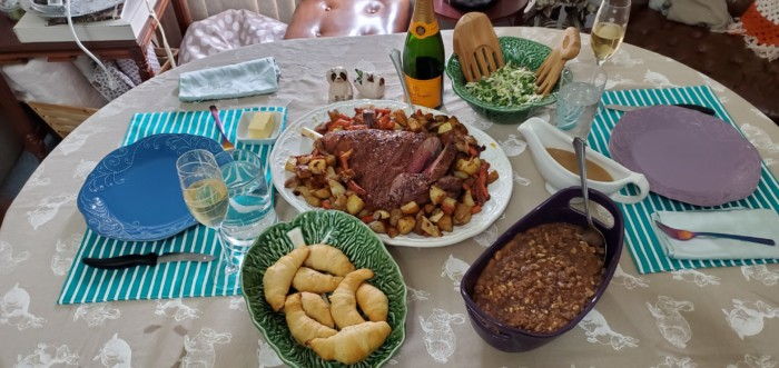 Easter dinner with lamb roast, vegetables, rolls, salad, sweet potato casserole, and champagne.