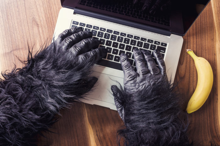 Gorilla hands typing on a computer with a banana snack