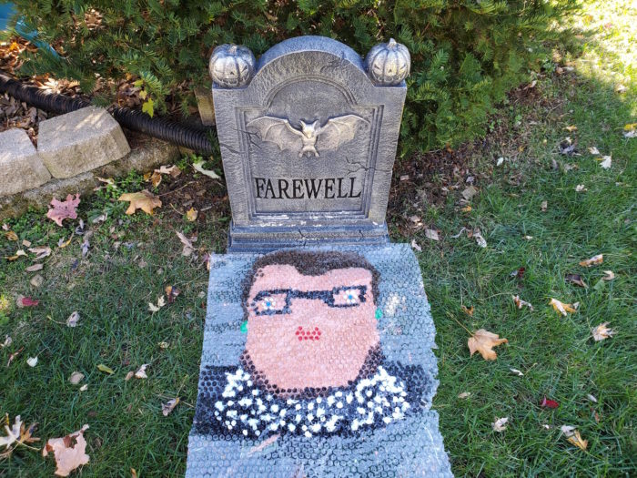A painting of RBG in bubble wrap in front of a Halloween tombstone